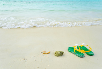 Green flipflop sandals on sea beach