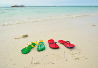 Colorful flipflop sandals on sea beach