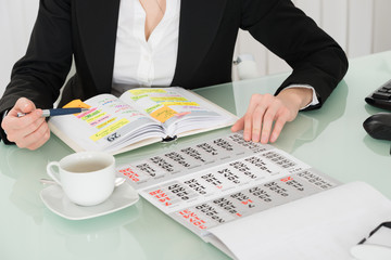 Fototapete - Businesswoman Reading List Of Work In Diary