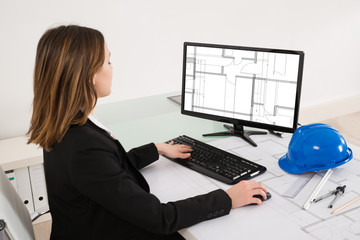 Female Architect Looking At Blueprint On Computer