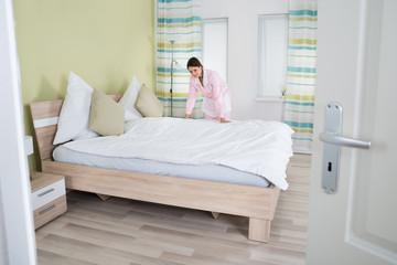 Female Housekeeper Making Bed