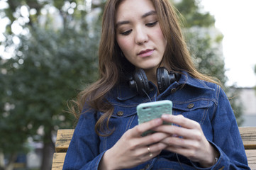 Young women are looking at the smartphone sitting on a bench in the park