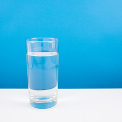 The tall glass of pure mineral water on a white table.