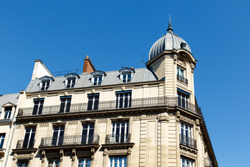 Color DSLR stock picture of an apartment building in the St. Germain neighborhood of Paris, France, with balconies a turret, and a blue sky background. The horizontal image has copy space for text