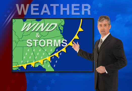 A tv television news weather meteorologist anchorman is reporting with a Wind & Storm graphic over a stormy black cloud photo on the monitor screen