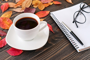 cup of black coffee with a notepad and pen