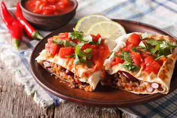 Mexican chimichanga with meat, vegetables and cheese close-up