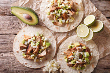 Carnitas Pork with onion and avocado on tortilla close-up. horizontal top view