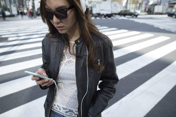 Young woman is walking at an intersection with a headphone