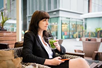 Senior business woman drinking mojito