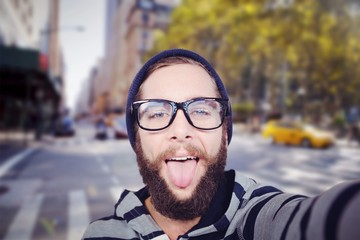 Composite image of portrait of happy hipster sticking out tongue