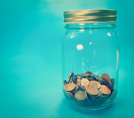 Glass jar with coins on blue background retro effect image