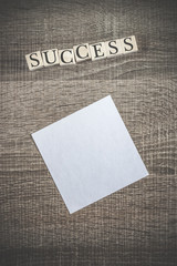 Success concept. Wooden blocks forming Success word on top of a blank paper