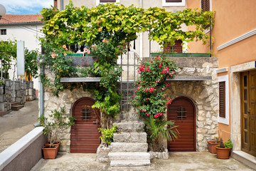 Doors and balconies full of of green plants and flowers in a traditional mediterranean house
