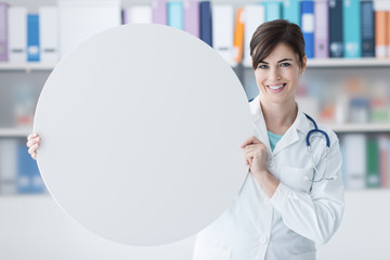 Smiling doctor holding a round sign