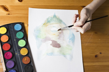 The artist paints a picture using brush and watercolor colorful painting set.  Hand with brush in process drawing watercolor image Wolf. Wooden background. Artistic retouching.