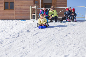 Two boys riding on sledge