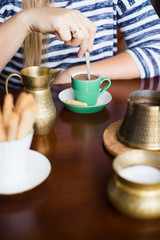 Woman stirring coffee with teaspoon. Selective focus