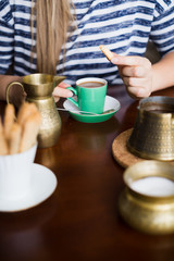 Woman drinking coffee with cookies. Selective focus