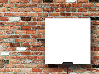Close-up of one square paper sheet on red and brown brick weathered brick wall background