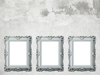 Close-up of three cyan baroque picture frames on stained concrete wall background