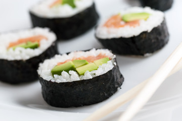 Sushi rolls with salmon, avocado, rice in seaweed and chopsticks on a plate.