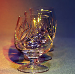 empty crystal glasses in colored light toning