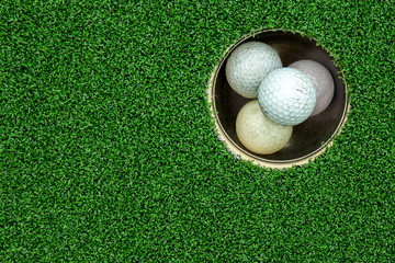 Top view of golf balls stacked up in green field
