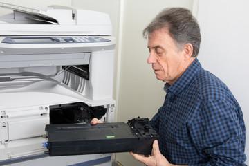 Man puts toner in the printer at office at work