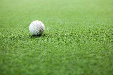 Golf ball on green field during sunset