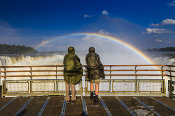 Travelers at Iguazu Falls. View of the rainbow and a waterfall.