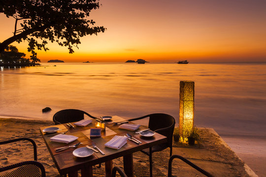 Romantic sunset on the shore of a tropical island. Cafe on the b