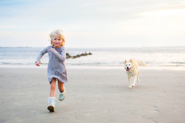Little Girl and Dog running on the beach
