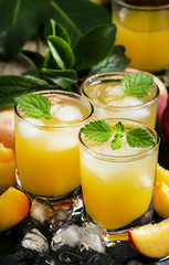 Cool summer peach juice with crushed ice, fresh peaches with lea