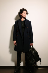 Handsome young man in a black coat with a black bag.