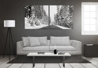 Winter art canvas on wall. Window, sofa, lamp, plant, glasses, book, coffee on table in living room interior.