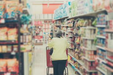 スーパーマーケットのショッピングカートを押す主婦