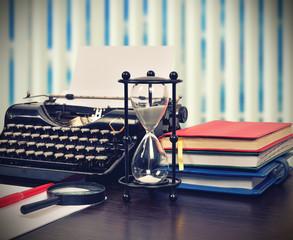 Hourglass, books and typewriter