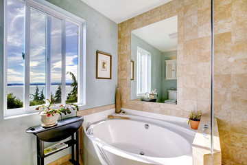 Oval tub with large mirror in luxury bathroom.