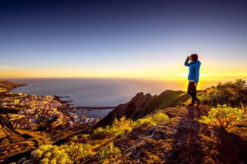 Deurstickers Canarische Eilanden Young female traveler in blue jacket enjoying landscape view on Santa Cruz city on La Palma island in the morning