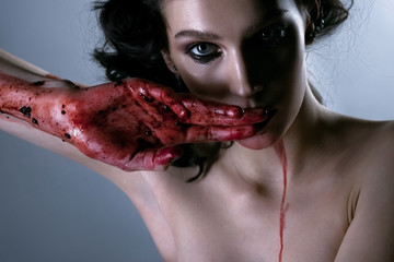 Beautiful portrait of young brunette woman with bloody hands. Ho