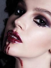 Closeup of bloody red lips young girl. Dark fashion beautiful br