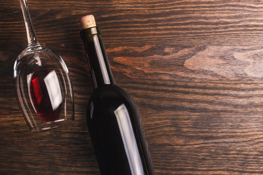 Glass with wine and bottle with cork, wooden background