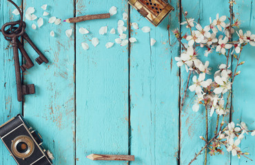 top view image of spring white cherry blossoms tree, old camera on blue wooden table