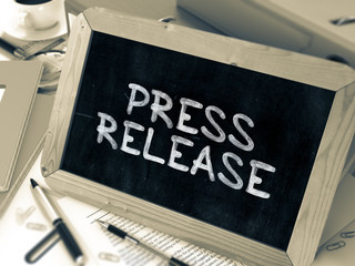 Press Release - Chalkboard with Hand Drawn Text, Stack of Office Folders, Stationery, Reports on Blurred Background. Toned Image. 3D Render.