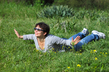 woman lying on a green grass