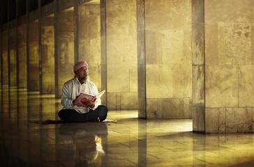 Religious muslim man reading holy koran Wall mural