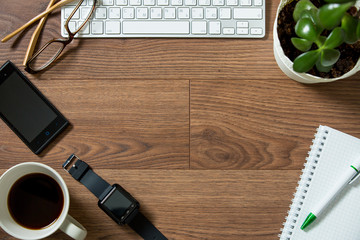 Business workplace from top, flay lay. Keyboard, smart watch, smart phone, glasses, plant, paper notebook, fresh morning coffee on the dark wooden desk