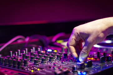 Dj mixes the track in the nightclub at party - music and technology concept