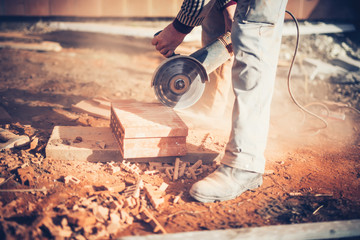 worker using an angle grinder on construction site for cutting bricks, debris. Tools and bricks on new building site